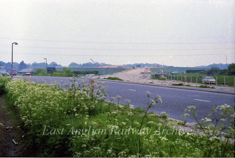 To the left the old route of the B1049 with the new road under construction to the right. The car in the distance, left, is at the old Arbury Road Junction.  21st May 1978