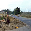 This part of the old Histon to Cambridge road will soon disappear for ever. View looking south towards Histon. The earth banks of the two slip roads can clearly be seen. In about a years time the A14 will wipe out this part of the road from left to right with the centre line being where the road sign is. Today the old road terminates here at the bank of the westbound slip road.  30th October 1977