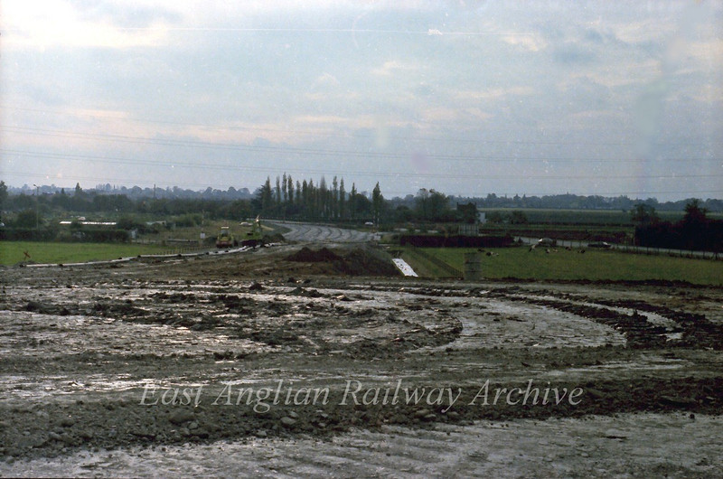 Looking from the area of the flyovers back towards Cambridge showing the new route of the B1049. The new junction for Kings Hedges Road is where the two diggers are. The old road runs to the right, the two cars showing the location of the old junction with Arbury Road.  30th October 1977
