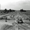 View looking West towards the Girton Interchange from the Histon bound flyover. Temporary traffic lights have been set up across the old route of the B1049. Two massive earth movers are crossing heading in the Milton direction.  17th July 1977