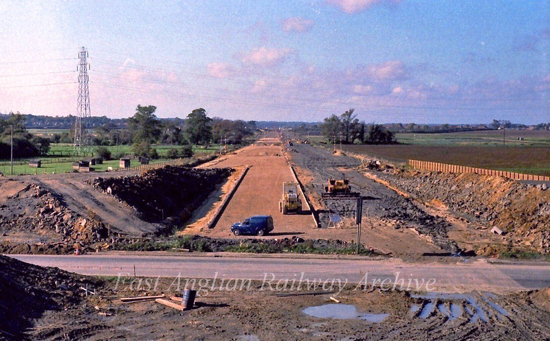 View west from the Histon bound flyover looking towards the Girton Interchange. The old B1049 Cambridge to Histon Road runs across the picture in the foreground. The two banks for the slip roads can clearly be seen with gaps for the old road.  26th December 1977.
