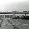 The view looking East towards Milton from a point West of the Histon bound flyover showing both flyovers. The old route of the B1049 runs behind   the hut. The roadsign in the centre marking the middle of the A14.  14th August 1977.