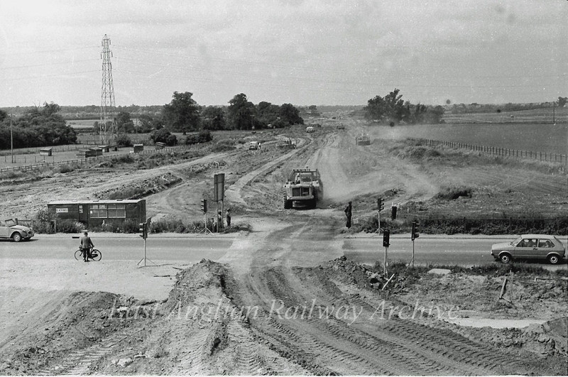 View west towards the Girton Interchange. Traffic is held up on the old route of the B1049. Viewed from Histon bound flyover.  17th July 1977