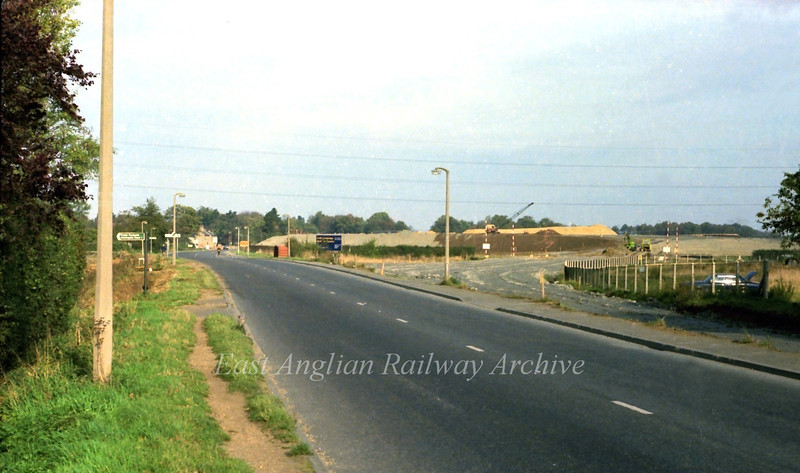 The scene on 30th October 1977. We are looking north towards Histon along the route of the old B1049 with the new road under construction to the right. The earth bank of the westbound slip road can be seen behind the blue sign.