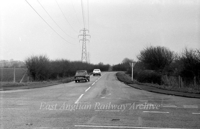 Arbury Road Junction with the old B1049. The new road comes across the field to the left and bisects the old road near the bend in the distance.  22nd February 1976.  The scene is unrecogniseable today.