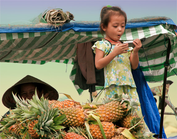A child on a Pineapple Boat in Vietnam plays with a mobile phone, as the grownups work to sell their fruit in a floating market