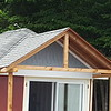 Cedar shakes are now on the back of the porch roof.  Now just the siding left.