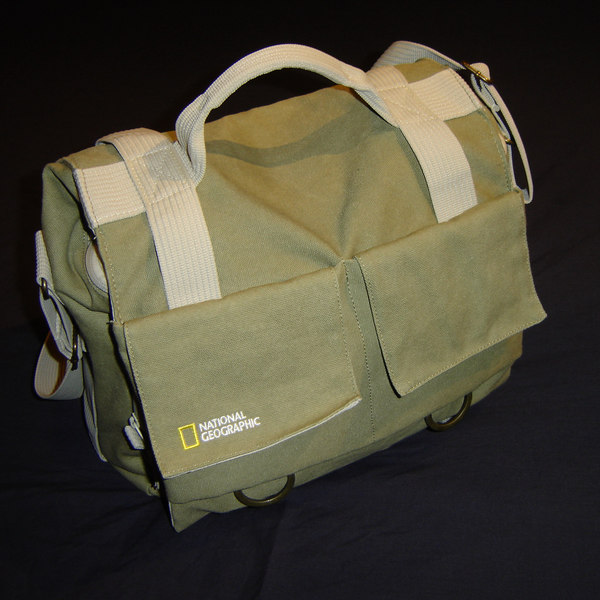 """This is the National Geographic Medium shoulder bag.  Made from, """"natures strongest fiber,"""" hemp.  It's very soft and lightweight; an ideal bag for just carrying one SLR and two or three lenses.  I refer to it as my """"indoor/outdoor light"""" bag.  It has a cool khaki color scheme with the National Geographic logo boldly displayed in front.  Equipped with two large pockets in front, which could hold a few filters and other things, and one in the back that could probably hold a composition notebook, it has a decent amount of exterior storage.  The two D-rings in front can be used to hang things off but I can't imagine that would be too comfortable.  This is one of those types of bags that at least partially depend on the contents to help it keeps its shape.  I think this bag would be perfect if you planned on carrying most of your gear on a plane in a rolling bag this would be a good bag to pack in you check-in baggage to be used once you got to your destination."""