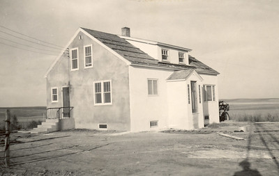 "I found this 1949 photo of ""the new house"" while trying to decide what style of front door to put in on the west (atop steps).  You can see the original stucco. It has since be replaced with light green vinyl siding (put on by Joe & Teresa in the 70s; destroyed in 1983 hailstorm) and tan Masonite (when we replaced all the windows and siding after that storm.   FYI: Brian was five weeks old when that storm hit with baseball and grapefruit-sized stones. His crib, beneath a north-facing window, was filled with glass shards afterwards. I had taken him and Jennifer to the basement to wait out the storm. Rob was in the dairy barn milking cows."