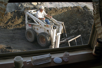 2007.6.24: View from the kitchen window as Rob continues to excavate dirt. You can see the bottles on the window sill that we found earlier. Another intact jar turned up today. Photo to follow once it's cleaned.
