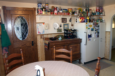 2006.6.26: North view of our present kitchen   Rob made the oak door, complete with etched, oval window. The buffet is a Campbell family heirloom. My collection of vintage tins and glass milk bottles stay put for the time being but will eventually be moving into the new kitchen.