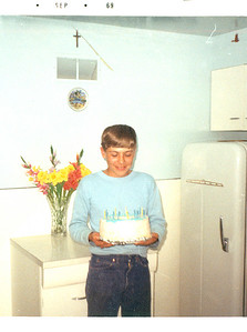 1969.7.16: Rob's 13th birthday. Photo taken in the kitchen. He's standing where our stove is now. The cabinet behind him is now where the fridge used to be.  Notice Grammy Teresa's lovely glads. What a green thumb she had!