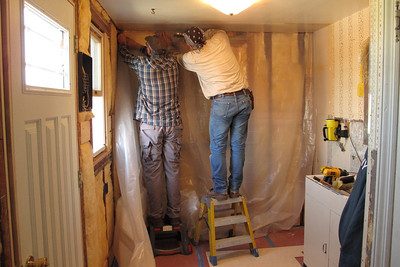 David and Rob stapling thick plastic over the fiberglass insulation ...