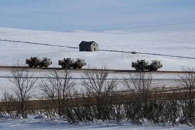 "Seismic Vibrator Vehicles   These strange-looking vehicles are used in petroleum exploration, referred to as seismographing. They've been roaming western North Dakota and eastern Montana since last fall, administering coordinated ""thumps"" with a center-mounted piston; the readings recorded by a network of cables strung in carefully prepared grids.   With powerful headlights and flashing warning lights, they were quite the sight this winter when days were short. I often wondered what folks passing through must have thought. They could easily have thought some sort of military mission was taking place or perhaps that aliens had landed.  We've had seismographers around before, but never with this type of vehicle. These machines are less invasive than bore-hole technology of the past."