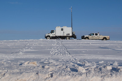 Seismic Recording Truck   The blue cord running through the snow to the truck is not an electric extension cord. It is part of the seismic grid.    The plentiful snow and fog we've had this winter has made the job utterly miserable for the crew.  A large percentage of them are from Brownsville, Texas; some are from Mexico; some from El Salvador.  They head out each morning in work groups of six per pickup, laying cable and batteries on top of the ground. That means digging through the snow or having a snowplow go ahead of them.   Men on snowmobiles and four-wheel utility vehicles replace the batteries as needed. Once they have the cable grid in place, then the vibes do their work, thumping diagonally across the terrain, the results recorded by instruments in trucks such as this.
