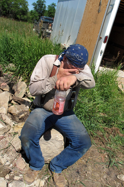 July 24, 2011<br /> Rob pauses for a Gatorade, sitting on the cornerstone that he helped me roll about half way to the cargo trailer.<br /> <br /> On a scale of ease and relaxation, salvaging rocks does not come in at a #10. Sweat drips and gets in your eyes, muscles complain, and dehydration is a concern.