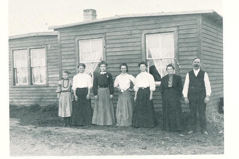 """L to R:  Edna Boyer, Goldie Boyer, Laura Brier--the teacher, Cora Boyer, Nellie Boyer, Mary Boyer, and Josepheus Boyer. The group is standing in front of the sod house, which was sided with wooden clapboards.<br /> <br /> """"In the spring of 1904, Mr. Boyer brought another emigrant car loaded with the rest of their belongings. Among those belongings was an umbrella with William McKinley's picture on it. Mr. Boyer had carried the umbrella in a parade in New York City when McKinley was campaigning for the presidency.""""<br /> <br /> """"The first crop of wheat raised was cut with a scythe, piled on the ground and then beat with a club. On a windy day it was lifted high and dropped slowly to let the wind blow the chaff away.. The club was soon replaced by a flail and then they really modernized by buying a grain binder and hiring it threshed. Some of the wheat was ground with an 1891 coffer grinder and made into bread. They raised a great variety of crops and the whole family helped with the farming. For raising the best corn, Edna won an all expense paid trip to the Agricultural College in Fargo and another to the Capitol in Bismarck and a dollar for spending money. Joseph Kitchen, County Superintendent from Sentinel Butte went along on the train."""""""