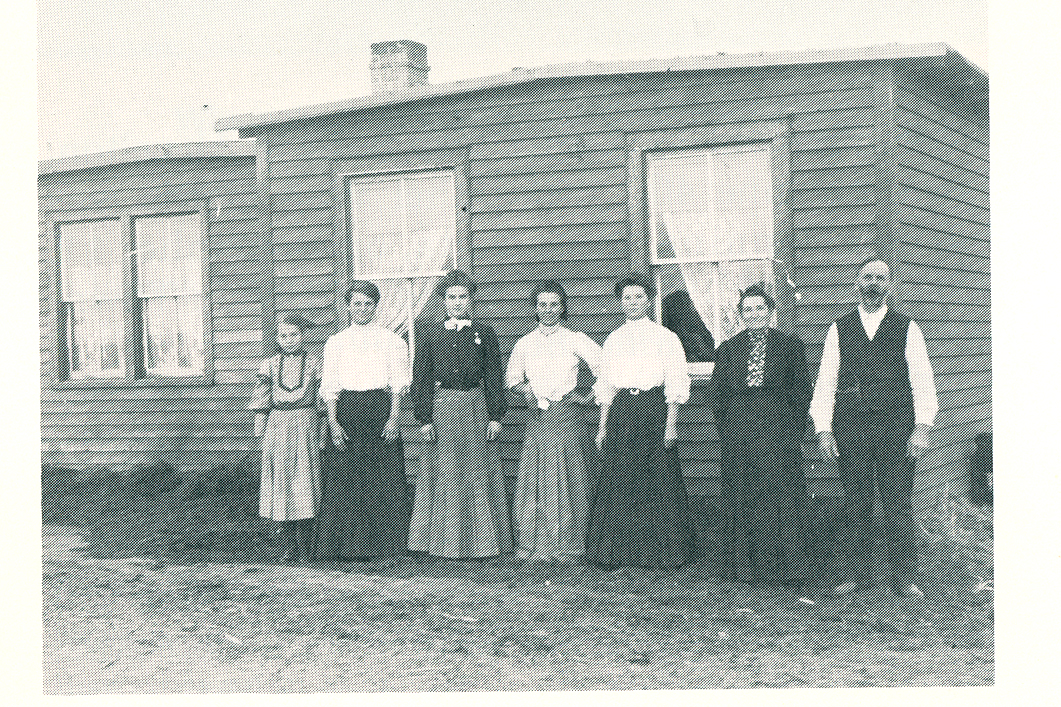 "L to R:  Edna Boyer, Goldie Boyer, Laura Brier--the teacher, Cora Boyer, Nellie Boyer, Mary Boyer, and Josepheus Boyer. The group is standing in front of the sod house, which was sided with wooden clapboards.<br /> <br /> ""In the spring of 1904, Mr. Boyer brought another emigrant car loaded with the rest of their belongings. Among those belongings was an umbrella with William McKinley's picture on it. Mr. Boyer had carried the umbrella in a parade in New York City when McKinley was campaigning for the presidency.""<br /> <br /> ""The first crop of wheat raised was cut with a scythe, piled on the ground and then beat with a club. On a windy day it was lifted high and dropped slowly to let the wind blow the chaff away.. The club was soon replaced by a flail and then they really modernized by buying a grain binder and hiring it threshed. Some of the wheat was ground with an 1891 coffer grinder and made into bread. They raised a great variety of crops and the whole family helped with the farming. For raising the best corn, Edna won an all expense paid trip to the Agricultural College in Fargo and another to the Capitol in Bismarck and a dollar for spending money. Joseph Kitchen, County Superintendent from Sentinel Butte went along on the train."""