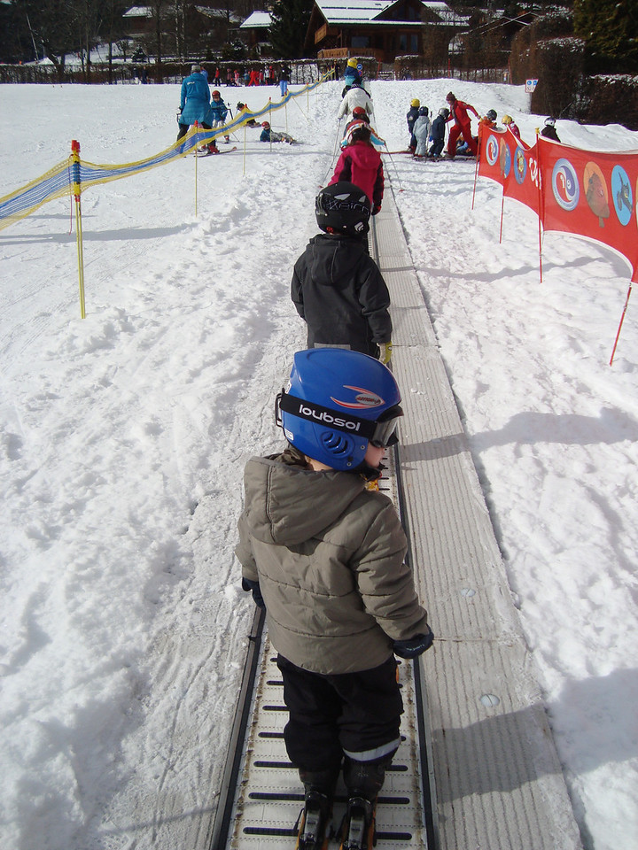 1st day skiing: taking both boys up the 'magic carpet' whilst Mike is parking the car