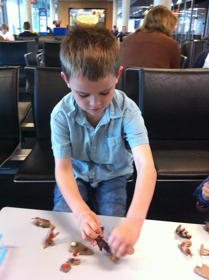 Jack playing with his new caveman toys @ Basel airport