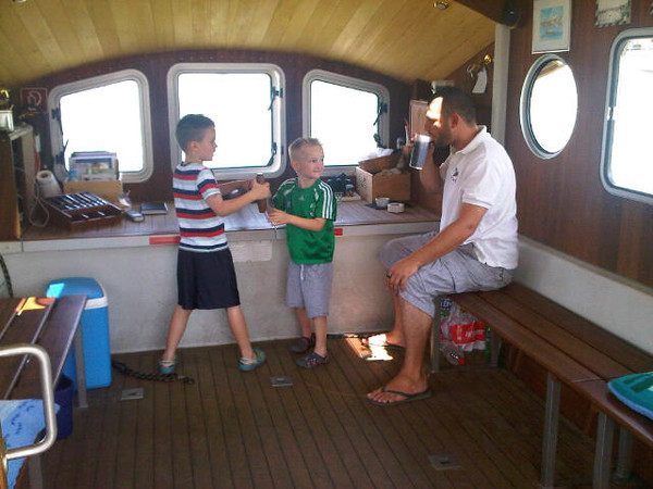 The nice ferry driver lets the boys steer