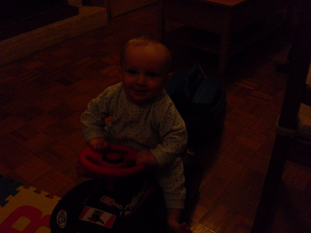 Our stupid camera broke, so this is a flash-less photo of Danny on the Bobby Car