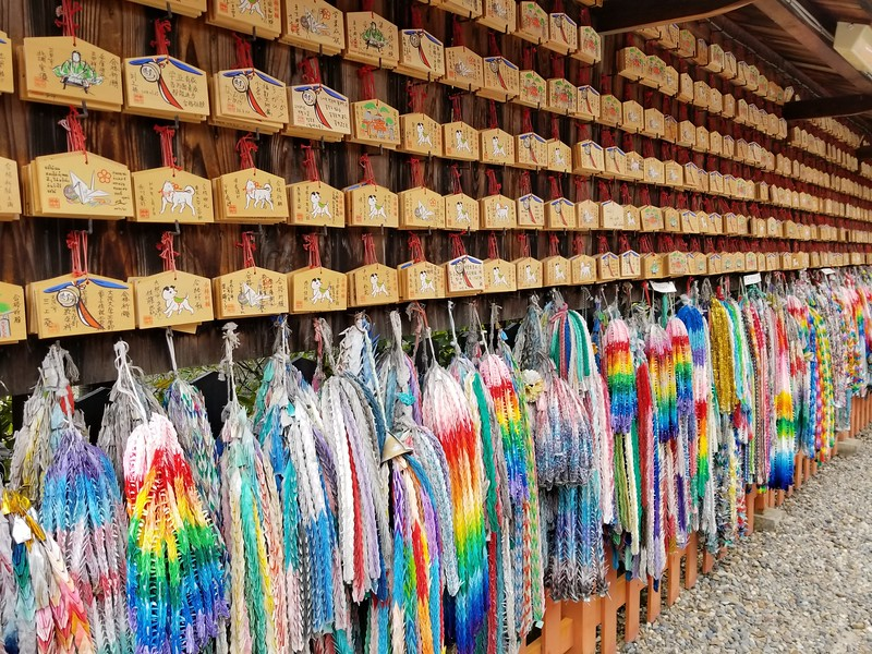 """Ema"" wishes on wood and colorful origami cranes in strings"