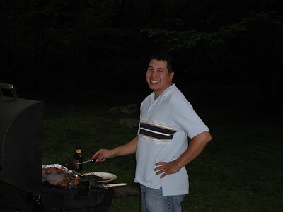 Michael cooking hotdogs for dinner.