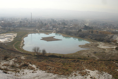 Pool of water from the hot springs with the village of Pamukkale in the background