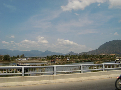 A bridge on the edge of town. Behind it are some of the hundreds of shrimp and fish farms that fill Cam Ranh Bay