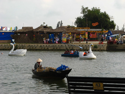 Paddle boats crowd the river flowing by the old town
