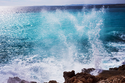 Beautiful turquoise sea, the mountains in the haze and the embankment of the Promenade des Anglais on a warm sunny day. Waves breaking on the rocks. Splashing water.