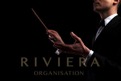portrait of young orchestra conductor performing with a baton while standing on black background
