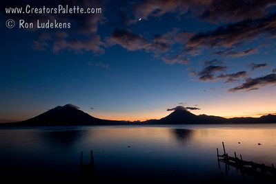Sunset over Lake Atitlan from Panajachel, Guatemala.   San Pedro Volcano on right with interesting cloud and Toliman Volcano with Atitlan Volcano behind it on left.  Sliver of moon starting to appear. Guatemala Mission Trip - Day 6 - Wednesday, November 14, 2007