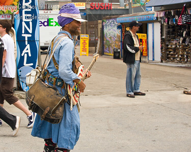 Rollerblading guitar player looking for donations. Bags hold speakers, amplifier and batteries as sound system for his guitar.