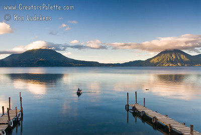 Sunrise on Lake Atitlan in Panajachel, Guatemala.  Toliman Volcano with Atitlan Volcano behind it on left, San Pedro Volcano on right.  Local fisherman in his boat made of planks.  He did a lot of bailing water. Guatemala Mission Trip - Day 7 - Thursday, November 15, 2007