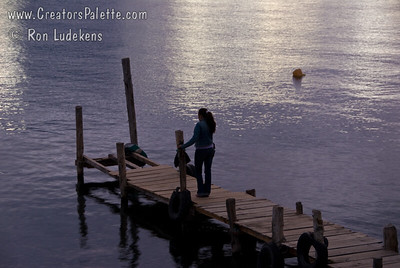Cell phone user on dock at sunset on Lake Atitlan in Panajachel, Guatemala. Guatemala Mission Trip - Day 5 -  Tuesday, November 13, 2007