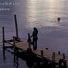 Cell phone user on dock at sunset on Lake Atitlan in Panajachel, Guatemala.<br /> Guatemala Mission Trip - Day 5 -  Tuesday, November 13, 2007