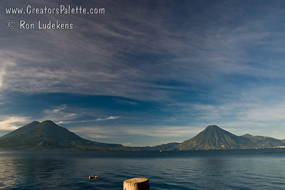 Early Morning along shore of Lake Atitlan in Panajachel.   The tiny orange dot in the middle of the photo way off in the distance is one of the 2 bouys the swimmers had to swim around.  Two volcanoes - Toliman in front with Atitlan behind it on left side, San Pedro Volcano on right side. Guatemala Mission Trip - Day 3 -  Sunday, November 11, 2007
