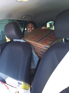 That is Brooke behind or UNDER the pizza. The rest of the trunk and seat next to her is filled with roasted chickens, cake, pies, mufffins that Price Mart donates to local orphanages.