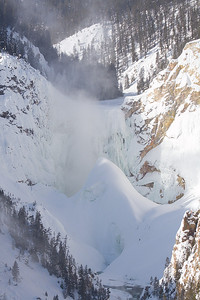 The Lower Falls of the Yellowstone River almost hidden behind huge cone of ice and snow.