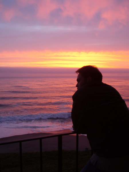Eileen's great photo of Matthew enjoying the sunset on the balcony of the condo. Every night, after dinner, Matthew would put on a coat and brave the cool breezes on the balcony reading until the sun would go down and he would not have light enough to read and then he would be deep in thought as the sun went down.<br /> <br /> P7210444-MatthewSunset-2 copy.jpg