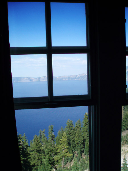 """Eileen's photo of the view from our Room 215 in the Crater Lake Lodge. We had an excellent view of Crater Lake (in the background), but we also had a good view of the patio restaurant directly below us. This actually turned out to be a mixed blessing because the patio was busy until late into the night and people were right below us on the patio drinking and laughing loudly. Then in the early morning, more people came out to the patio for breakfast and coffee and the noise started up again. Ah the joys of sleeping with the windows open!<br /> <br /> The Crater Lake Lodge was an excellent place to stay, comfortable, great views from the room, but the patio noise was not that great. Why did we have the windows open? Because the lodge does NOT have air conditioning!!! As they told us when we checked in, """"the lodge does not have air conditioning or telephones to preserve the initial flavor of the original lodge as built in 1915"""". How quaint... But it was still a great stop for us.<br /> <br /> P7250509-CraterLakeViewFromInsideLodgeRoom215-2 copy.jpg"""