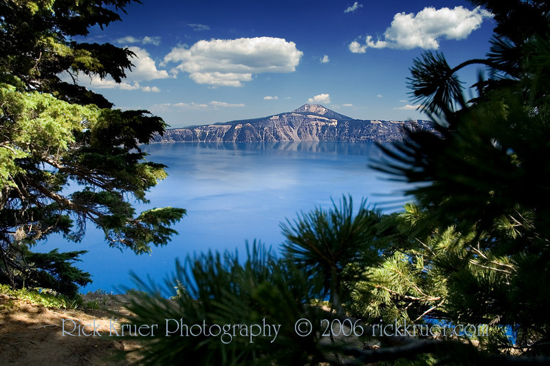 Crater Lake framed by the tall pines on the edge of the lake. Altitude is 7351 feet (2240 meters) here. Photo taken looking toward the east.<br /> ND70_2006-07-26DSC_6014-CraterLakeTreeFrameMerriamPointWestSideLookingEast-nice-6 copy.jpg