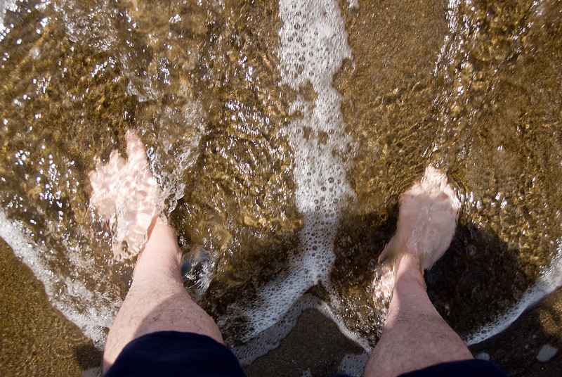 Rick's feet get wet as the ocean lets us know who is boss.<br /> D200_2007-07-12DSC_1516-RickWetFeet-2.jpg