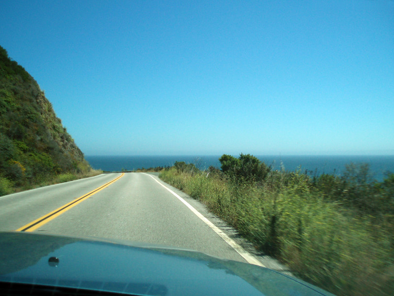 The road ahead of us as we enjoy a new scenic view around each corner.<br /> P7252070-RoadAheadWithOceanView-2.jpg