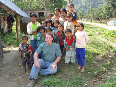 VBTours' Gene Miller sitting with Bru children in village near Khe Sanh.