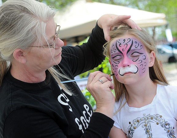 "Erica Hildinger (right) patiently waits for Jan Cates, from Magic Mirror, to finish her face painting during the YWCA ""A Day Without Violence"" activities Saturday. (Staff Photo by BONNIE VCULEK)"