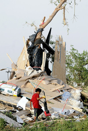 Harley Voyager removes a vacuum cleaner from the tornado-ravaged home of Jeremy and Crystal Sullins Tuesday after the new double-wide trailer was destroyed northwest of Longdale. The Sullins' family, who was returning home after a trip to Oklahoma City, was not injured. (Staff Photo by BONNIE VCULEK)