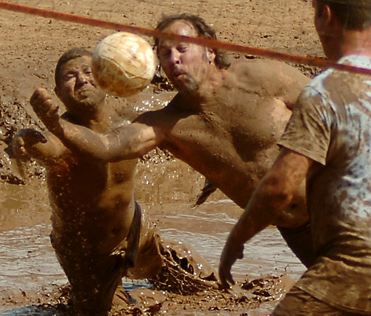 Rum Boat team members dive for a return volley during the championship game at the Enid Miracle League Mud Volleyball Tournament Saturday, August 02, 2014. Proceeds from the event support baseball activities for children and adults with special needs. (Staff Photo by BONNIE VCULEK)